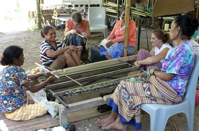 Women sharing turns at the loom
